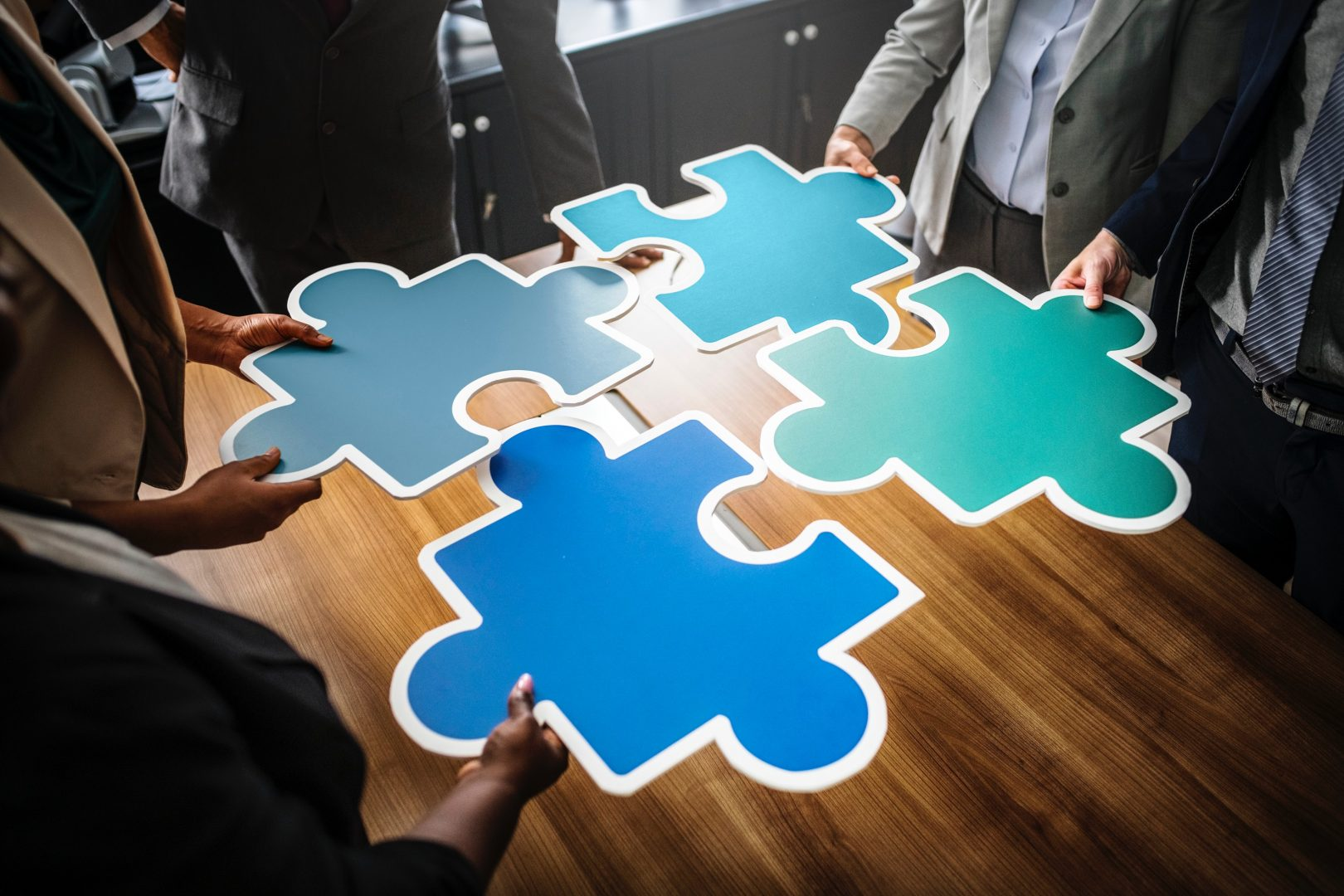 Four people putting together big blue puzzle pieces